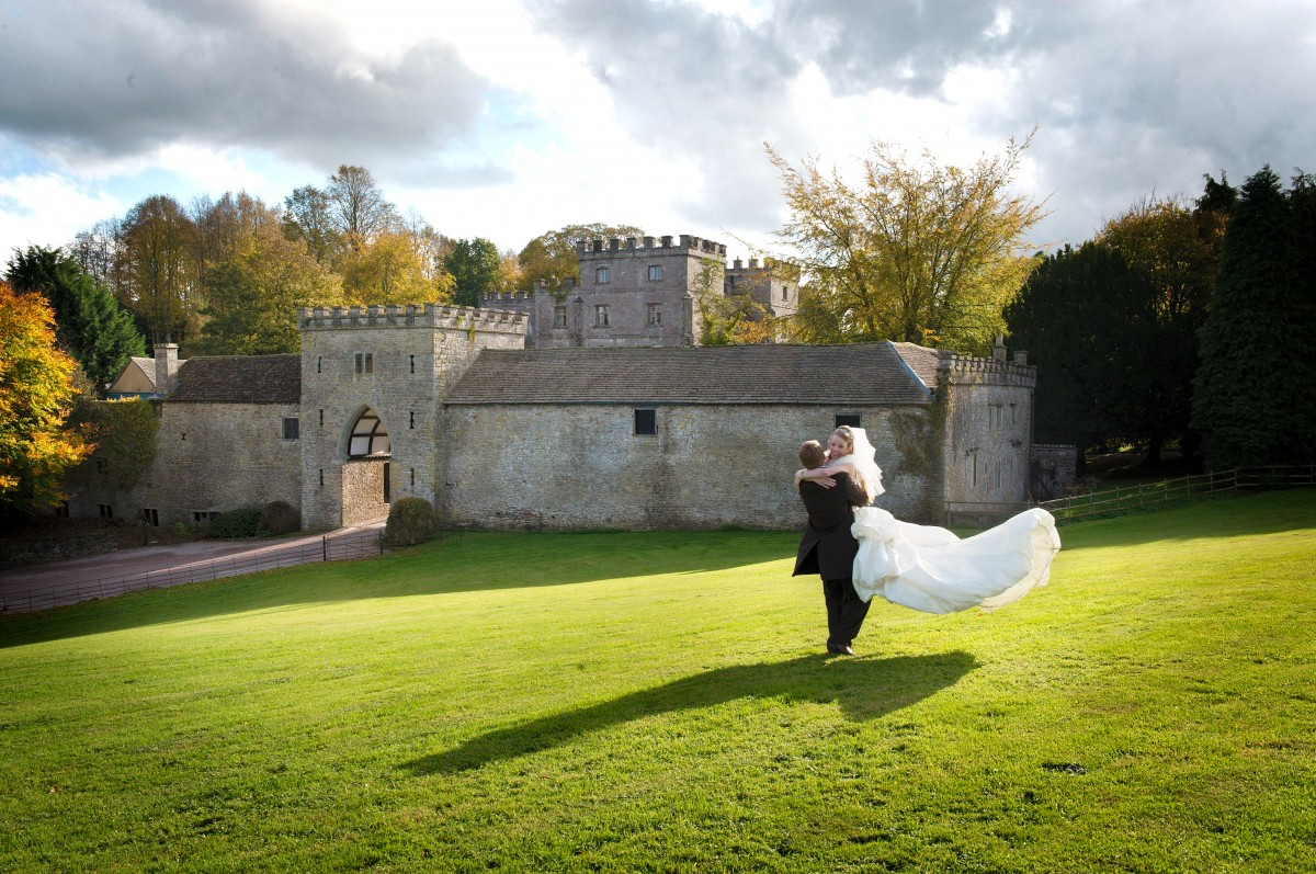 Country House WeddingsClearwell- couple having fun in front of Portcullis